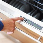 woman pressing energy saver button on dishwasher