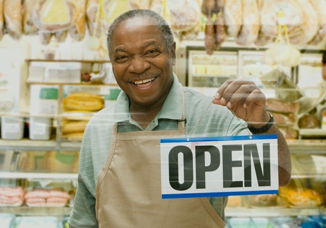 man holding a business open sign