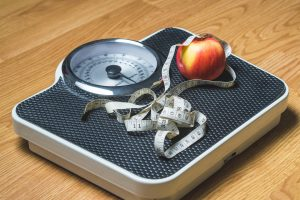 Weight Loss Weighing scale and an apple and a tape measure